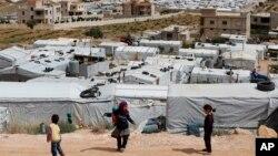 Anak-anak pengungsi Suriah bermain di dekat kamp pengungsi sementara yang dibangun di antara permukiman penduduk dan bangunan-bangunan lainnya di Arsal, perbatasan Suriah-Lebanon timur, 13 JUni 2018. (Foto: dok).