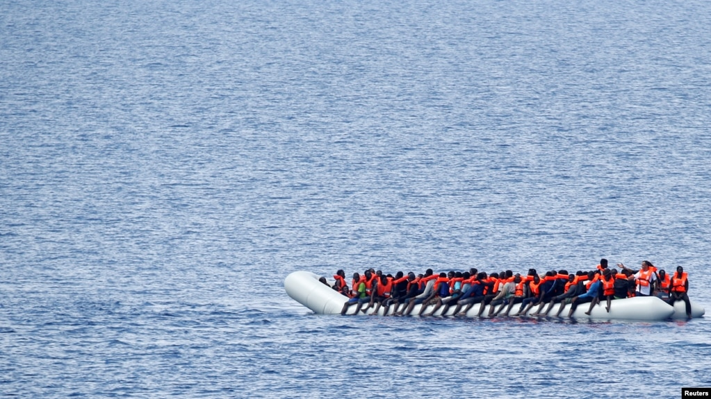 FILE - Migrants are seen in the Mediterranean Sea off the coast of Libya, June 18, 2017. As many as 70 migrants drowned Friday when their boat capsized off the Tunisian coast.