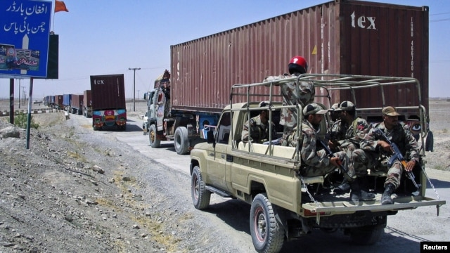 Paramilitary soldiers escort a convoy of trucks carrying supplies for NATO troops in Afghanistan, before crossing into Afghanistan from Pakistan, July 16, 2012.