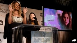 "Presenters Laverne Cox, left, and Awkwafina announce Lady Gaga as a nominee for outstanding performance by a female actor in a leading role for ""A Star is Born"" as Cox gives the Little Monsters monster claw hand gesture during the nominations announcements for the 25th annual Scr"