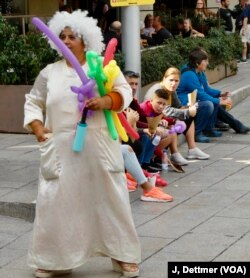 Clowns sell balloons to tourists in a Barcelona plaza: the biggest decision tourists have to make in Barcelona's medieval Gothic Quarter each day is which restaurant to pick.