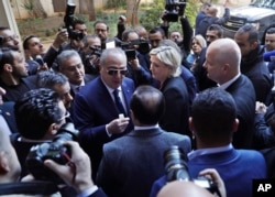 French far-right presidential candidate Marine Le Pen, center, leaves Dar al-Fatwa building, the headquarters of the Sunni Mufti, after she refused to wear a head scarf to meet with Lebanon's Grand Mufti Sheikh Abdel-Latif Derian, in Beirut, Lebanon, Feb. 21, 2017.