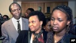 Léon Mugesera (à gauche) sort d'un tribunal à Québec, le 12 avril 2001, en compagnie de sa femme (au c.) et de sa fille (à dr.)