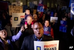 FILE - Activists and protesters with the National Center for Transgender Equality rally in front of the White House, Feb. 22, 2017 after President Trump announced he would revoke guidelines for protecting transgender students.