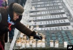Một người sống sót sau vụ Diệt chủng thắp nến cầu nguyện cho các nạn nhân trong buổi lễ đánh dấu 69 năm giải phóng trại tử thần ở Auschwitz ở Oswiecim, Ba Lan, 27/1/2014