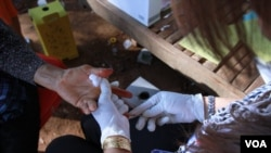 A Cambodian health agent pricks the finger of a woman who sought an HIV blood test service in Peam village, Muk Kompoul district, Kandal province, Feb 22, 2016. (Aun Chhengpor/VOA Khmer)