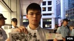學民思潮成員黎汶洛,展示去年參與反國教集會照片,及主動查詢被低調通緝的報案編號 (湯惠芸攝)