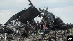 Proruski borci skupljaju municiju iz olupine ukrajinskog vojnog aviona koji su srušpili blizu aerodroma u Lugansku