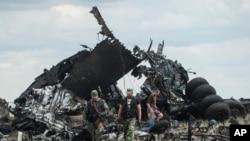 亲俄罗斯的战斗人员在他们击落的军用运输机残骸处搜集弹药