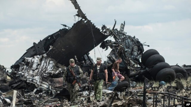 Pro-Russian fighters collect ammunition from the site of remnants of a downed Ukrainian army aircraft Il-76 at the airport near Luhansk, Ukraine, Saturday, June 14, 2014.