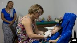 Caio Julio Vasconcelos yang lahir dengan microcephaly menjalani terapi fisik di Joao Pessoa, Brazil (25/2). (AP/Andre Penner)
