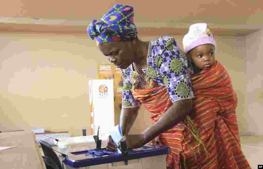 A woman with a child on her back casts her vote at a polling station as the country goes to the polls in Maputo, Mozambique.