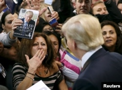 FILE - A woman blows a kiss to Republican presidential candidate Donald Trump (R) after Trump autographed her chest at his campaign rally in Manassas, Virginia, Dec. 2, 2015.