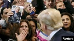 Tư liệu - Một người phụ nữ hôn gió ứng cử viên Đảng Cộng hòa Donald Trump (phải) sau khi ông ta ký tên lên ngực bà ta tại một buổi vận động ở thành phố Manassas, bang Virginia, ngày 2 tháng 12, 2015.