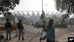 A sweeper cleans the surroundings as security guards stand guard outside the Jawaharlal Nehru stadium, the main venue of the Commonwealth Games early in the morning in New Delhi, India, 26 Sept. 2010.