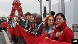 Climate activists carry a red banner during a demonstration at the COP21, United Nations Climate Change Conference, in Le Bourget, north of Paris, Friday, Dec. 11, 2015. (AP Photo/Michel Euler)