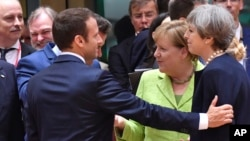 French President Emmanuel Macron (left) puts his hand on the shoulder of British Prime Minister Theresa May during a round table meeting at an EU summit in Brussels, June 22, 2017. German Chancellor Angela Merkel stands between them.
