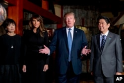 U.S. President Donald Trump, accompanied by first lady Melania Trump, second from left, Japanese Prime Minister Shinzo Abe and his wife Akie Abe, left, speaks to members of the media before having a dinner at Ginza Ukai Tei restaurant, Nov. 5, 2017, in To