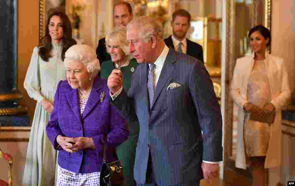 Britain's Prince Charles, Prince of Wales (C), walks with his mother, Britain's Queen Elizabeth II (2L), and his wife, Britain's Camilla, Duchess of Cornwall (3L), and his sons and their wives, Britain's Prince William, Duke of Cambridge (4L) and Britain's Catherine, Duchess of Cambridge (L), and Britain's Prince Harry, Duke of Sussex, (2R) and Meghan, Duchess of Sussex (R), during a reception to mark the 50th Anniversary of the investiture of the Prince of Wales at Buckingham Palace in London.