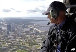 FILE - In this Sept. 12, 2017 photo, Gov. Rick Scott assesses flooding damage over Jacksonville, Florida, in the aftermath of Hurricane Irma.
