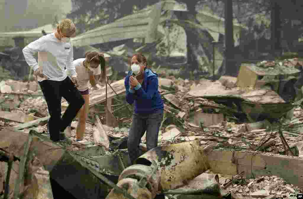 Mary Caughey, center in blue, reacts with her son Harrison, left, after finding her wedding ring in debris at her home destroyed by fires in Kenwood, California.