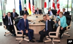 Japanese Prime Minsiter Shinzo Abe, foreground center left, and U.S. President Barack Obama, foreground center right, smile at photographers with other leaders of Group of Seven industrial nations, clockwise from left, French President Francois Hollande,