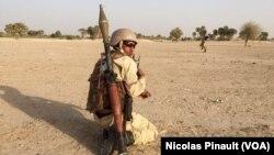 Un soldat nigérien porte un lance-roquette sur son dos, dans le camp d'Assaga, le 29 février 2016. (VOA/Nicolas Pinault)