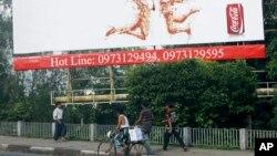FILE - People walk under a huge advertising billboard of Coca-Cola in downtown Yangon, Myanmar.
