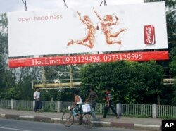 FILE - People walk under a huge advertising billboard of Coca-Cola in downtown Yangon, Myanmar.