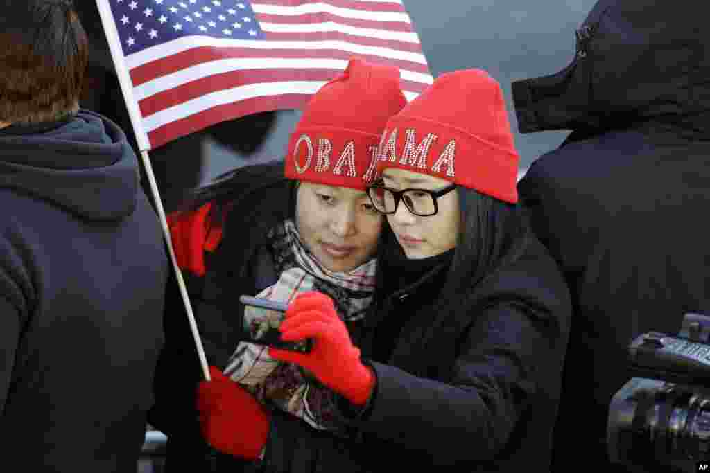 Khongorzul Battsengel, left, and Ariunbolor Davaatsogt both from Mongolia, take a picture of themselves as they wait for President Barack Obama in the 57th Presidential Inaugural Parade on Pennsylvania Ave. in Washington D.C., Jan. 21, 2013.