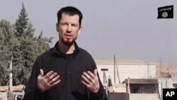 FILE - In this still image taken from an undated video published on the Internet by the Islamic State group militants, captive British journalist John Cantlie speaks into a camera in what he identifies as the embattled Syrian town of Kobani.
