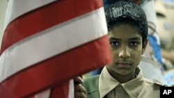 Boy Scout Omar Farooq, 12, presents the US flag for the pledge of allegiance to an audience of all faiths at the All Dulles Area Muslim Society mosque in Sterling, Virginia, March 6, 2011