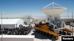 Workers and visitors gather around a vehicle loading a parabolic antenna during the Atacama Large Millimetre/Submillimetre Array (ALMA) observatory inauguration, east of Calama, Chile, Mar. 13, 2013.