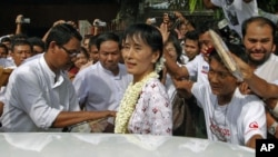 Burma pro-democracy leader Aung San Suu Kyi leaves the National League for Democracy head office after a news conference to mark the first anniversary of her release from house arrest, in Rangoon, November 14, 2011.