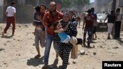 Người Palestine ôm con nhỏ chạy trốn các vụ ném bom của Israel vào Gaza, ngày 9/7/2014.