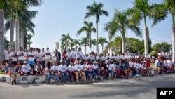 """Warga Timor Leste mengenakan kaus berslogan """"VIVA Timor Leste"""" berkumpul di depan kantor pemerintah untuk menyambut Perdana Menteri Scott Morrison di Dili, 30 Agustus 2019. (Foto: AFP)"""