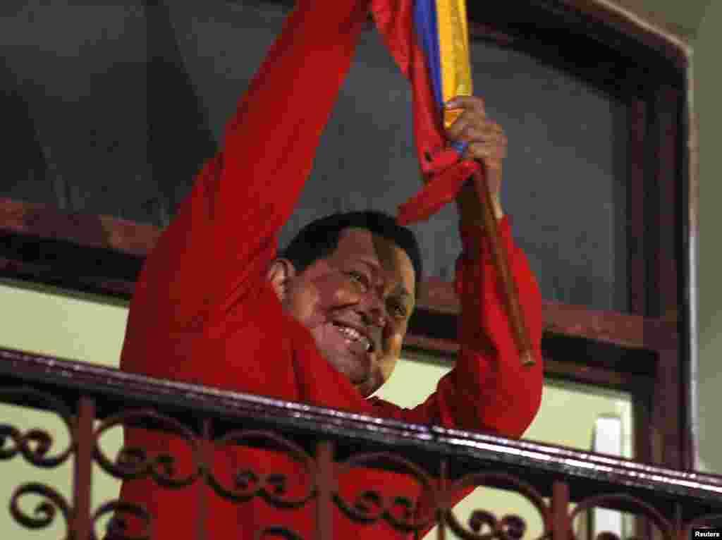ປະທານາທິບໍດີ Venezuela ທ່ານ Hugo Chavez ຈັບທຸງຊາດ ຂະນະທີ່ສະຫລອງໄຊຊະນະ ຢູ່ລະບຽງ ປາສາດ Miraflores ຫລືທໍານຽບປະທານາທິບໍດີ ທີ່ນະຄອນຫລວງ Caracas, ວັນທີ 7 ຕຸລາ 2012.