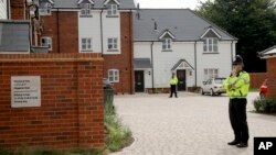 """British police officers stand outside a residential property in Amesbury, England, July 4, 2018. British police have declared a """"major incident"""" after two people were exposed to an unknown substance in the town."""