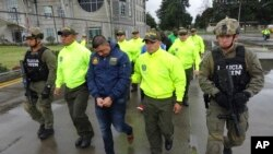 FILE - This undated photo released by Colombia's National Police shows officers escorting a man whom police identified as Ecuadorean drug trafficker Washington Edison Prado after his April 2017 arrest on an indictment by a Florida federal court. Colombia's chief prosecutor's office said Feb. 24. 2018, that it had extradited Prado to the United States.