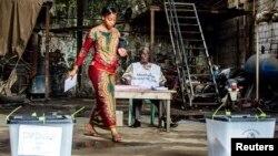 Une électrice s'apprêtant à déposer son bulletin dans un bureau de vote dans le quartier Madina de la capitale guinéenne, Conakry, le 28 septembre 2013.