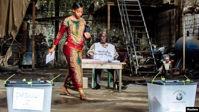 A voter prepares to cast her ballot at a polling station in the Madina neighbourhood of Guinea's capital Conakry, Sep. 28, 2013.