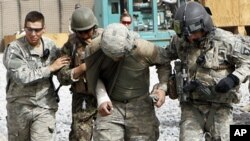 FILE - An Afghan soldier and a U.S. soldier were injured by a roadside bomb blast, Sept. 18, 2010. Such blasts can cause to traumatic brain injuries and internal bleeding. Researchers are looking at ways to better treat such injuries.