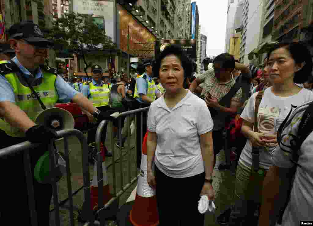 Former Hong Kong Chief Secretary Anson Chan (center) looks on beside a police officer as she joins thousands of protesters during a march to demand universal suffrage in Hong Kong, July 1, 2014.
