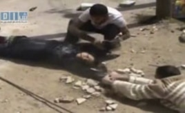This amateur video image shot on April 24, 2011 and made available by SHAAM News Network and posted on Youtube, May 12, 2011, shows two men crawling close to the ground and dragging a woman to safety in Daraa, Syria
