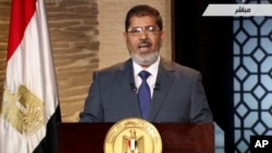 In this image taken from Egypt State TV, newly-elect President Mohammed Morsi delivers a speech in Cairo, Egypt, Sunday, June 24, 2012. In his first televised speech on state TV, Morsi pledged Sunday to preserve Egypt's international accords, a reference