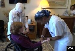 Kelli Wilson takes a patient's pulse, as nursing professor Linda Hall looks on.
