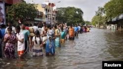 Dân cư lội qua một con phố bị ngập lụt khi sơ tán nhà cửa ở Chennai, tại bang miền nam Tamil Nadu, Ấn Độ, ngày 03/12/2015.