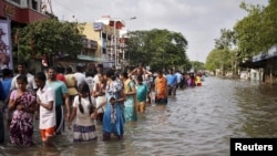 Residents wade through a flooded street as they evacuate their homes in Chennai, in the southern state of Tamil Nadu, India, Dec. 3, 2015.