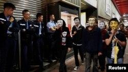 Demonstran pro-demokrasi yang menggunakan topeng Guy Fawkes melewati polisi di distrik Mongkok, Hong Kong (5/11). (Reuters/Bobby Yip)