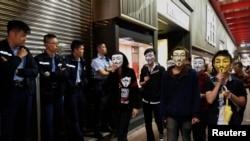 Người biểu tình đòi dân chủ mang mặt nạ Guy Fawkes đi ngang qua cảnh sát trên con đường bị chiếm đóng ở khu vực Mongkok, Hong Kong, ngày 5/11/2014.